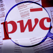 A magnifying glass examines the PwC logo surrounded by auditing documents