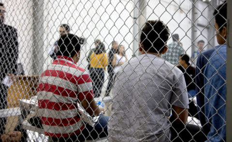 Detainees sit in a cell against a chain link fence.