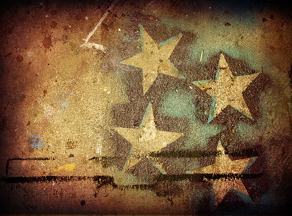This is a graphic like photograph of gold stars that have been painted via stencil.