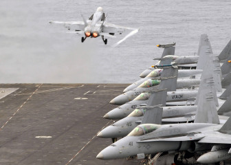 This photograph is of a Navy Fighter Plane F-18 taking off of the U.S. Abraham Lincoln aircraft carrier while at sea.