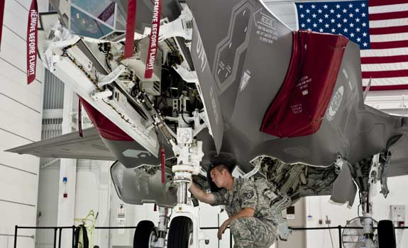 Photograph of the F-35 being worked on the underside.