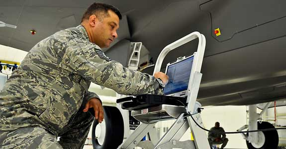 Photo of Airmen with computer plugged into the plane