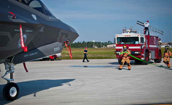 Eglin Air Force Base firefighters move toward a 33rd Fighter Wing F-35 Lightning II during a major accident response.
