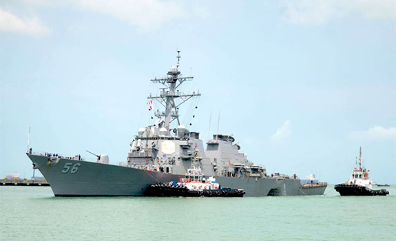 USS John F. McCain limps into Singapore in August after a collision with a merchant vessel blew the hole in its side that is visible between the two tugboats.