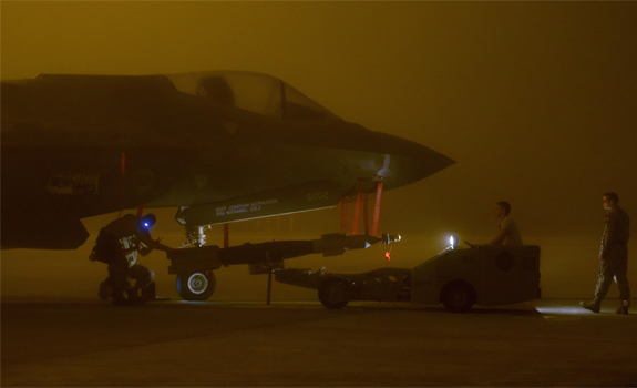 An Air Force weapons load crew loads a live GBU-12 into an F-35A Lightning II