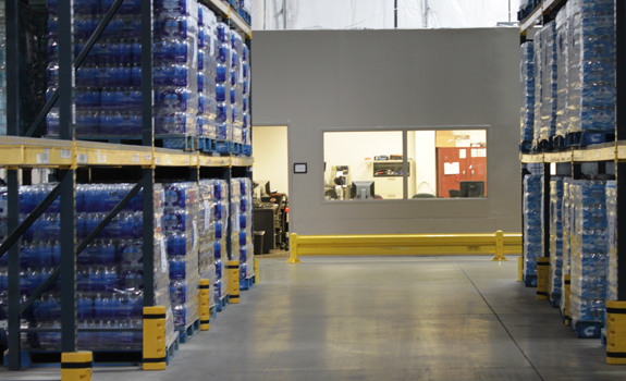 An office in a FEMA warehouse surrounded by pallets of water.