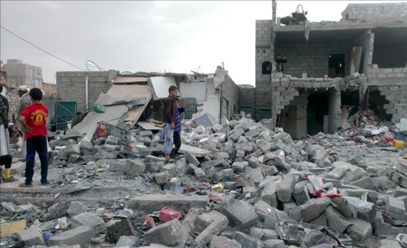 Survivors search through the rubble of buildings left after an airstrike, San'a, Yemen.